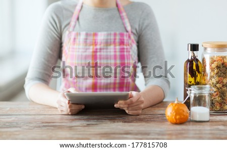 cooking, technology and home concept - closeup of woman reading recipe from tablet pc computer - stock photo