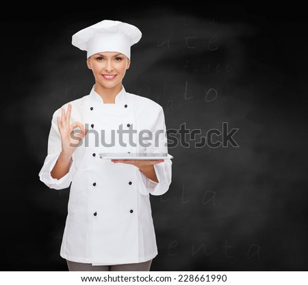 cooking, technology and people concept - smiling female chef, cook or baker with tablet pc computer showing ok gesture over blackboard background - stock photo