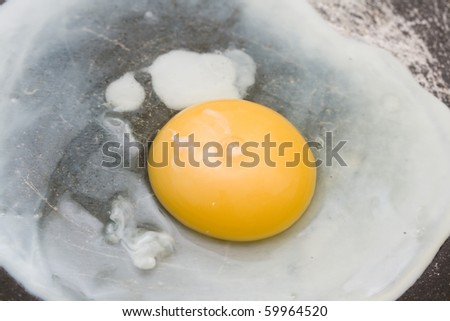 cooking the egg in the frying pan close-up