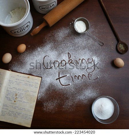 Cooking time, Cooking time text written on the flour with some ingredients around - stock photo