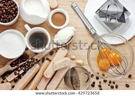 Cooking tiramisu concept, ingredients for making italian dessert on wooden table, process of preparation traditional cake top view - stock photo