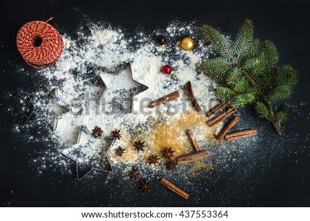 Cooking traditional Christmas holiday gingerbread cookies with cinnamon on black background, top view - stock photo