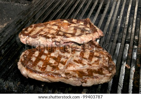 cooking two steaks on the grill