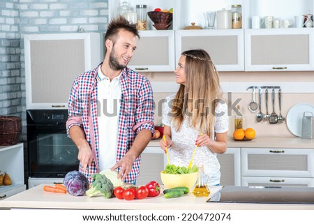 Cooking Useful food. Young and beautiful couple in love cooking at each other while preparing dinner with vegetables in the kitchen. - stock photo