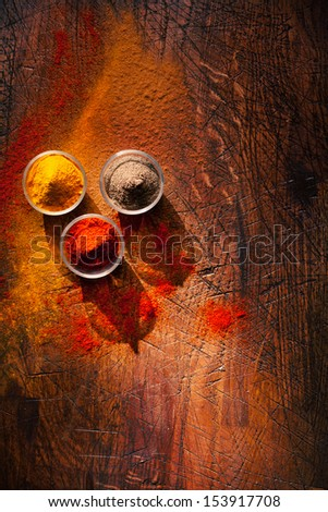 Cooking using fresh ground spices with three small bowls of spice on a wooden table with powder spillage on its surface, overhead view with copyspace - stock photo