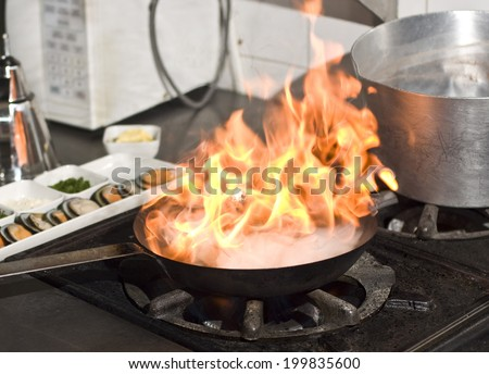 Cooking with flame in a frying pan - stock photo