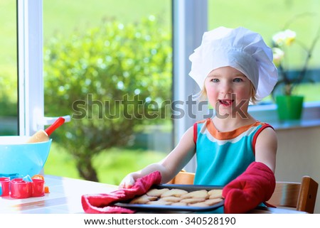 Cooking with kids. Little happy child, adorable toddler girl in white chef hat helping mother baking delicious pastry in the kitchen. - stock photo