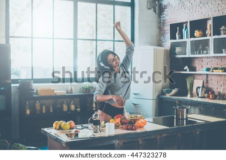 Cooking with passion. Beautiful young mixed race woman in headphones cooking salad and dancing while standing in kitchen at home - stock photo
