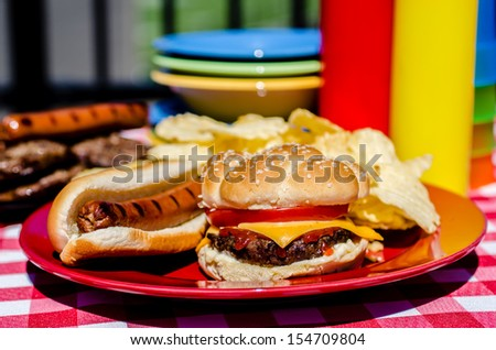Cookout with cheeseburger, hot dog and potato chips.  Mustard and ketchup bottles, bowls, hamburger patties, and hot dog wieners in background. - stock photo