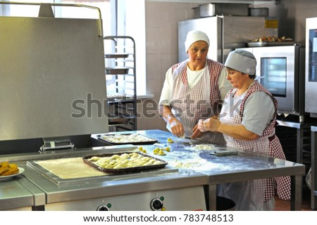 Cooks make dumplings standing behind the kitchen counter. Day of opened door for mass-media in the Ukrainian parliament canteen. November 23. 2017. Kiev, Ukraine