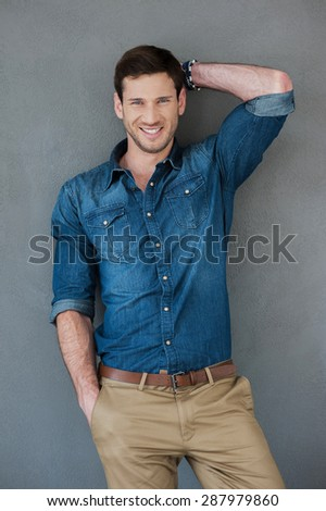 Cool and casual. Smiling young man posing while standing against grey background - stock photo