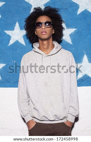 Cool and casual. Young African man in sunglasses standing against American flag - stock photo