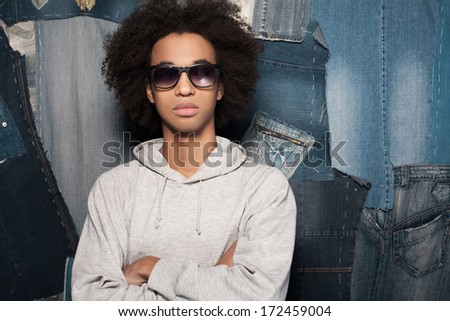 Cool and casual. Young African man in sunglasses standing against jeans background - stock photo