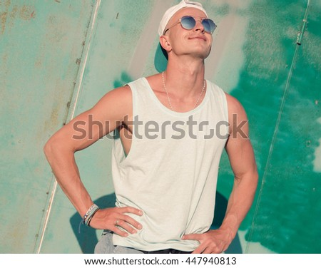 Cool and handsome. Handsome young man in sunglasses keeping arms crossed and looking away while standing in front of the textured wall outdoors