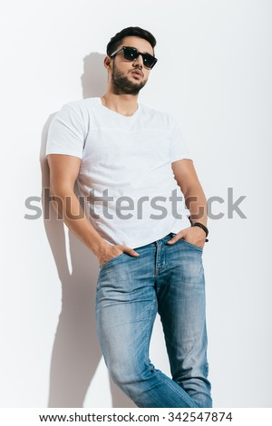 Cool and handsome. Low angle view of handsome young Indian man in sunglasses holding hands in pockets and looking away while standing against white background - stock photo