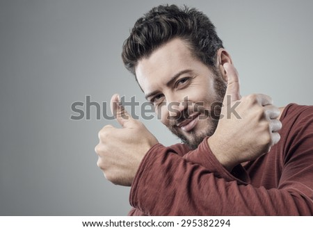 Cool attractive guy thumbs up smiling at camera