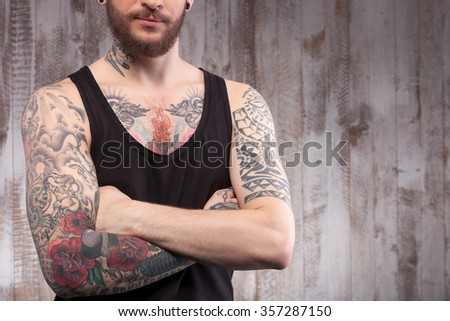 Cool bearded hipster is standing with crosses arms near a wall. The tattooed man is posing with confidence. Copy space in right side - stock photo