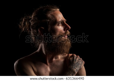 Cool bearded hipster on black background in studio photo. Expression and fashion