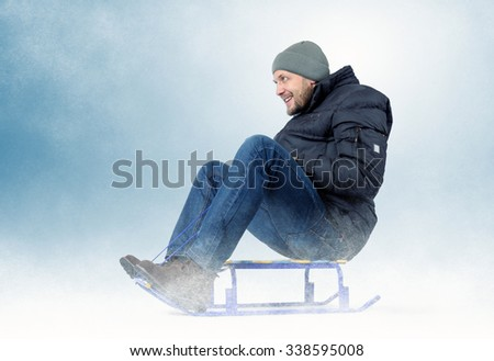 Cool bearded man on a sled in the snow, concept snow fun - stock photo