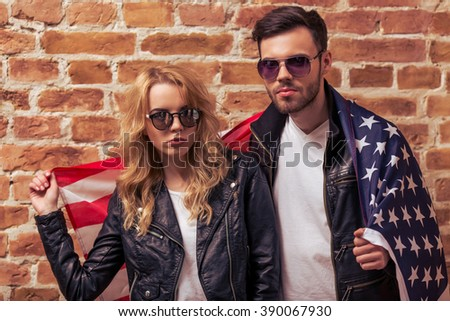 Cool beautiful young couple in leather jackets and sunglasses is looking at camera, standing covered with American flag against brick wall