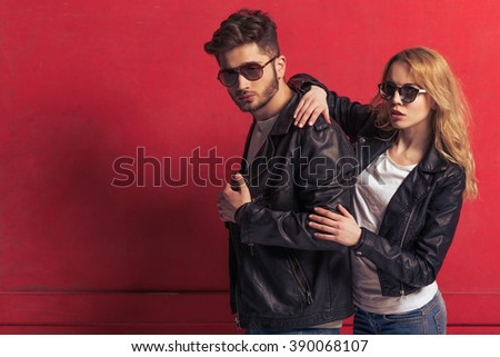 Cool beautiful young couple in leather jackets and sunglasses is looking at camera, standing against red background