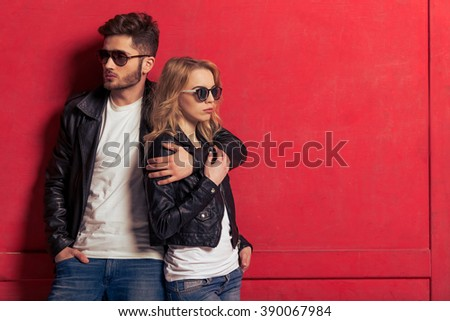 Cool beautiful young couple in leather jackets and sunglasses is looking away and hugging, standing against red background