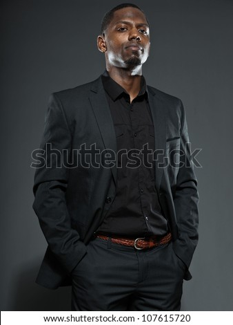 Cool black american man in dark suit. Studio fashion shot isolated on grey background. - stock photo