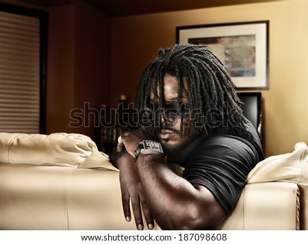 cool black man with dreads on leather couch. - stock photo