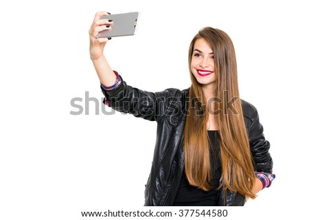 Cool blonde teenage girl in black leather jacket smiling, taking a selfie on smartphone. Beautiful young woman photographing herself using cellphone. Horizontal, isolated on white, copy space. - stock photo