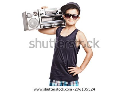 Cool boy in hip hop outfit holding a ghetto blaster over his shoulder and looking at the camera isolated on white background