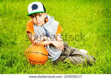 Cool boy lying on a grass with a basketball at a park. Summer day.