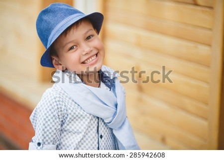 Cool boy wearing hat and jacket stands at a park and smiles. Summer day. Holiday.caucasian little boy in a summer hat outdoors - stock photo