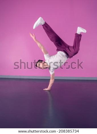 Cool break dancer doing handstand on one hand in the dance studio - stock photo