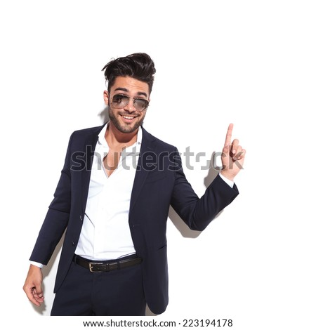 Cool business man wearing sunglasses smiling and pointing up, having a good idea, against a white background - stock photo