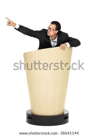 Cool businessman pointing on lectern on isolated white - stock photo