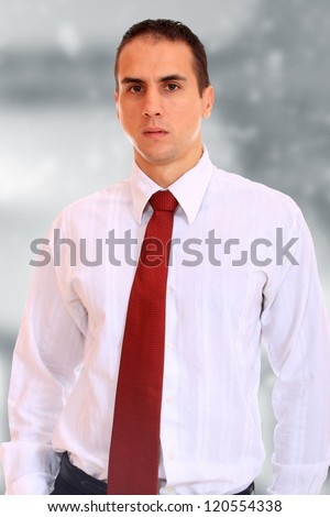 Cool businessman standing on light  background - stock photo