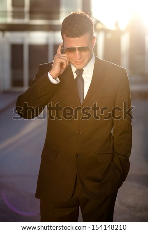 Cool businessman taking a call in front of an office building - stock photo