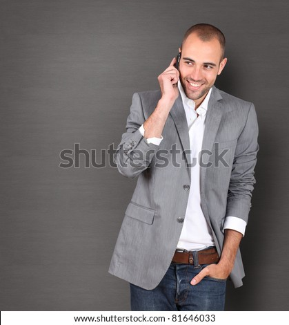 Cool businessman talking on mobile phone - stock photo