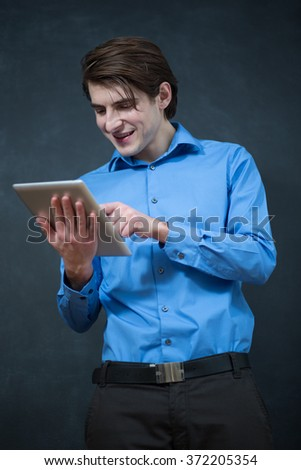 Cool businessman using electronic tablet on chalkboard  background - stock photo