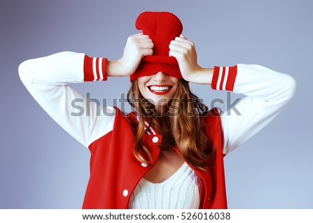 Cool cheerful girl with bright red lips wears modern knitted cap and sport jacket. Hipster style. Youth fashion.