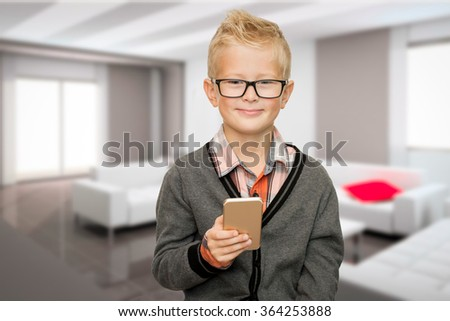 cool cute young boy child holding mobile smart phone in living room - stock photo
