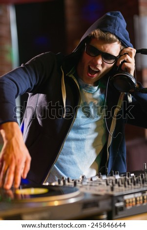 Cool dj spinning the decks at the nightclub - stock photo