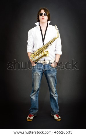 Cool dude posing with a saxophone strapped around his neck - stock photo