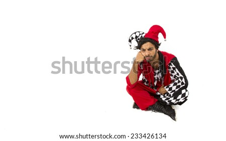Cool Eastern European guy dressed in a red white and black jester costume with a hat posing sat down on the floor looking fed up - stock photo