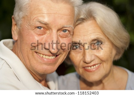 Cool elderly couple in the garden on a background of green trees and bushes