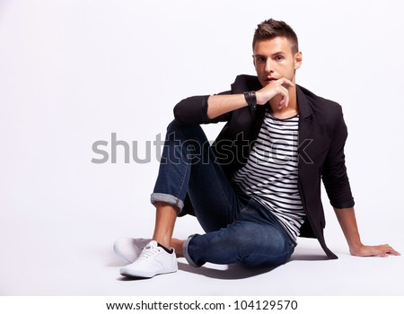 cool fashion male model sitting on grey background and looking at the camera
