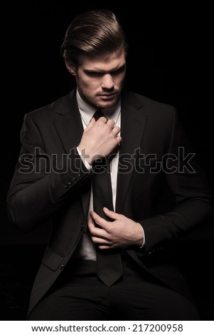 Cool fashion man in blue shirt and sunglasses sitting with his hand in pocket, smiling and looking away.  - stock photo