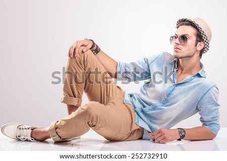 cool fashion man lying on the floor, holding one knee up, looking away from the camera.