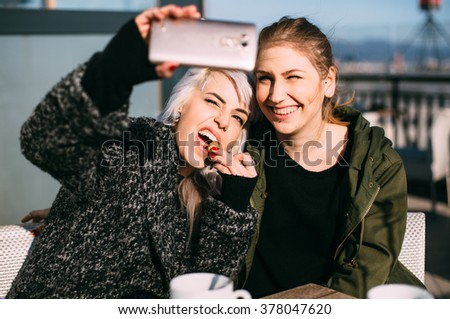 Cool fashionable girls taking a selfie in coffee shop - stock photo