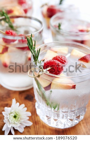 Cool fruity cocktails/soda water served on a wooden tray decorated with flowers, raspberries, sliced nectarine and garnish - stock photo